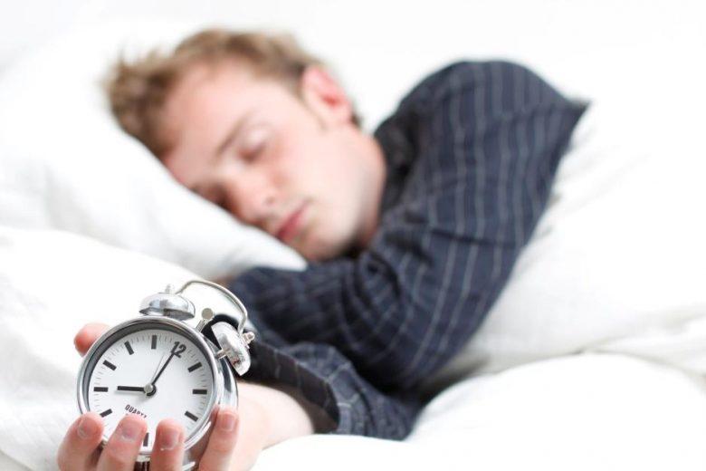 hombre durmiendo con un despertador