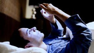 hombre con móvil en la mano antes de dormir